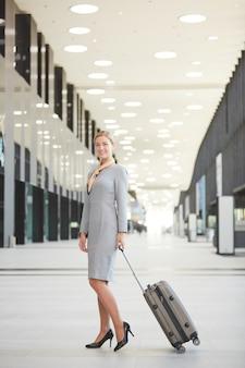 Retrato vertical de corpo inteiro de mulher loira elegante com mala e sorrindo em pé no aeroporto