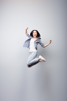Retrato vertical de corpo inteiro de mulher louca pulando