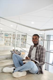 Retrato vertical de corpo inteiro de um estudante afro-americano ouvindo música enquanto está sentado de pernas cruzadas na escada na faculdade e fazendo o dever de casa.