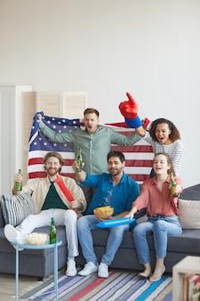 Retrato vertical de corpo inteiro de um grupo multiétnico de amigos assistindo a uma partida de esportes na tv e torcendo emocionalmente enquanto segura a bandeira americana