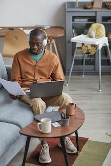 Retrato vertical de corpo inteiro de um homem afro-americano moderno usando um laptop e usando fones de ouvido enquanto trabalha em casa, sentado no sofá