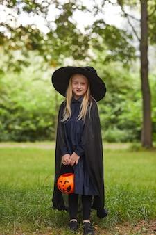 Retrato vertical de corpo inteiro de uma adolescente sorridente vestida de bruxa posando ao ar livre e segurando um balde de halloween