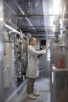Retrato vertical de corpo inteiro de uma jovem mulher operando unidades de máquina enquanto trabalhava em uma fábrica de alimentos industriais