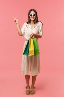 Retrato vertical de corpo inteiro, linda garota feminina indo às compras, usando óculos escuros e vestido, segurando sacolas da loja e apontando o dedo para a esquerda, sugiro visitar o próximo shopping