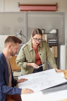 Retrato vertical de dois arquitetos olhando plantas e discutindo o trabalho em pé perto de uma mesa de desenho em um escritório moderno