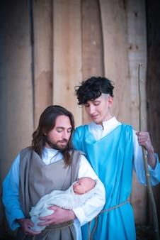 Retrato vertical de dois homens representando a virgem maria e josé em um presépio segurando um bebê