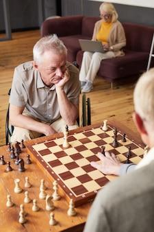 Retrato vertical de dois homens sêniors jogando xadrez e desfrutando de atividades em uma aconchegante casa de repouso