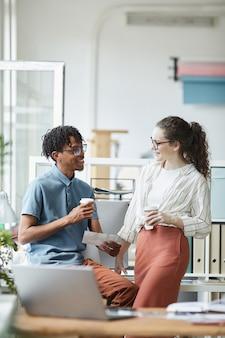 Retrato vertical de dois jovens criativos olhando fotos impressas e conversando durante o intervalo para o café em um escritório moderno