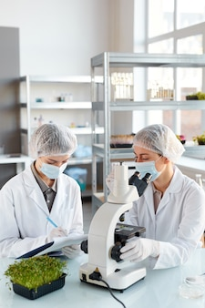 Retrato vertical de duas jovens cientistas olhando no microscópio enquanto estudam amostras de plantas no laboratório de biotecnologia