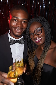 Retrato vertical de elegante casal afro-americano olhando para a câmera enquanto festeja em uma boate