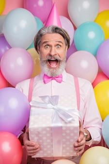 Retrato vertical de homem animado comemorando segurar caixa de presente sobre fundo rosa