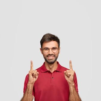 Retrato vertical de homem bonito e feliz com a barba por fazer levanta o dedo indicador