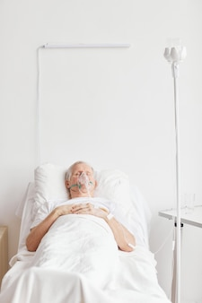 Retrato vertical de homem idoso doente, deitado em uma cama de hospital com máscara de suplementação de oxigênio e olhos fechados, copie o espaço