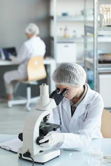 Retrato vertical de jovem cientista olhando no microscópio enquanto estuda amostras de plantas no laboratório de biotecnologia