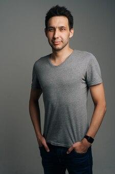Retrato vertical de jovem confiante em pé de camiseta cinza com as mãos nos bolsos em fundo escuro isolado. foto de estúdio de homem branco, vestindo roupas casuais, posando olhando para a câmera.