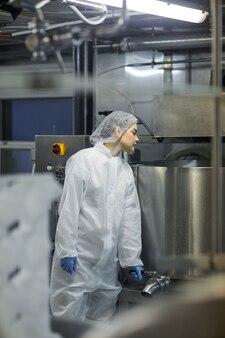 Retrato vertical de jovem trabalhadora usando máquinas na fábrica de produção de alimentos limpos, copie o espaço