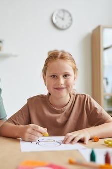 Retrato vertical de menina ruiva sardenta sorrindo enquanto desenha com giz de cera durante a aula de arte na escola