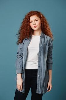 Retrato vertical de mulher adolescente bonita com cabelos ruivos ondulados e sardas em camiseta branca e casaco de lã cinza, posando para o álbum de formatura da escola com expressão feliz.