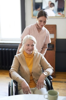 Retrato vertical de mulher jovem ajudando mulher idosa sorridente em cadeira de rodas em uma casa de repouso