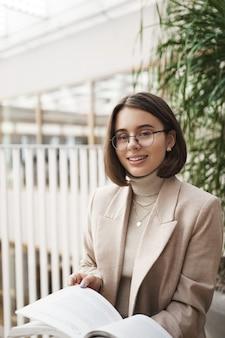 Retrato vertical de mulher jovem e atraente elegante de óculos e blazer, sentada no corredor, centro de negócios, ensinando língua estrangeira, preparar lição de casa ou material para as próximas aulas a ensinar.