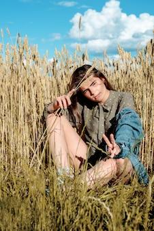 Retrato vertical de mulher jovem e bonita no campo. garota em espigas de trigo no campo quente de verão adolescente ao ar livre, moda e modelo.