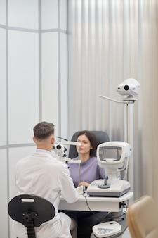 Retrato vertical de mulher jovem usando máquinas durante teste de visão em clínica de oftalmologia moderna