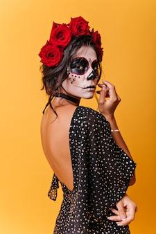Retrato vertical de mulher mexicana com rosas na cabeça. menina com máscara de carnaval posando pensativa