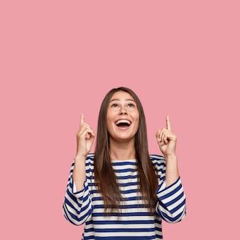 Retrato vertical de mulheres alegres de cabelos escuros apontando com ambos os dedos indicadores para cima, mostra o espaço livre
