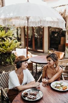 Retrato vertical de mulheres bronzeadas em roupas da moda, sorrindo e conversando em um aconchegante café de rua