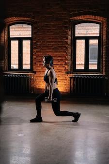 Retrato vertical de musculoso jovem mulher atlética com belo corpo forte vestindo roupas esportivas, fazendo agachamento e segurando halteres. treino feminino de fitness caucasiano fora exercitando-se no ginásio escuro.