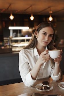 Retrato vertical de romântico feminino jovem bebendo café sozinho em um café aconchegante.