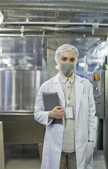 Retrato vertical de trabalhadora usando máscara e segurando a prancheta enquanto controla a produção na fábrica de alimentos