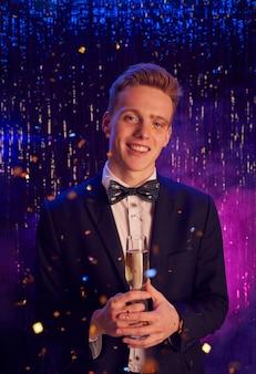 Retrato vertical de um adolescente loiro segurando uma taça de champanhe e sorrindo para a câmera enquanto aproveita a festa à noite