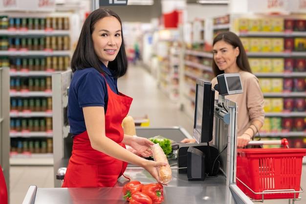 Retrato vertical de um caixa asiático atraente usando avental vermelho, trabalhando no caixa, emitindo sinais sonoros para o cliente