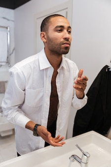 Retrato vertical de um homem africano lavando uma camisa no banheiro de um hotel
