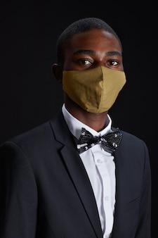 Retrato vertical de um homem afro-americano elegante usando máscara facial enquanto posa contra um fundo preto na festa