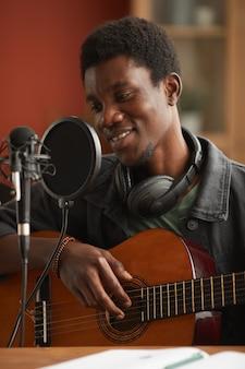 Retrato vertical de um homem afro-americano talentoso cantando ao microfone e tocando violão enquanto grava música no estúdio