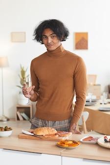 Retrato vertical de um homem mestiço contemporâneo segurando uma taça de champanhe enquanto cozinha para jantar dentro de casa