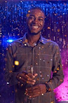 Retrato vertical de um jovem afro-americano segurando uma taça de champanhe e sorrindo para a câmera enquanto aproveita a festa na boate