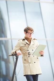 Retrato vertical de um jovem moderno vestindo sobretudo e lendo documento enquanto se inclina sobre uma scooter elétrica em um ambiente urbano com edifícios de vidro no fundo, copie o espaço