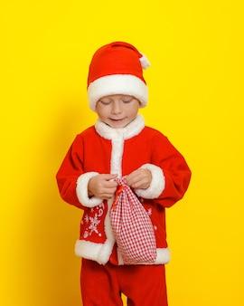 Retrato vertical de um menino vestido de papai noel que está prestes a abrir uma sacola com presentes