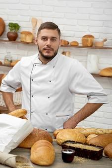 Retrato vertical de um padeiro profissional que levanta em sua compra da padaria que vende o conceito tradicional orgânico natural saudável saudável delicioso de compra da pastelaria do alimento.