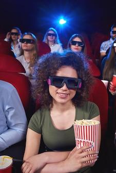 Retrato vertical de uma bela jovem sorrindo apreciando a estréia do filme 3d no cinema segurando pipoca sentado relaxado atividade divertida espectador espectador positividade tecnologia.
