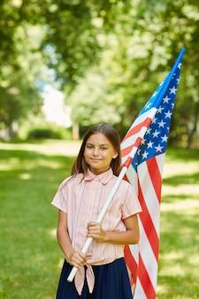 Retrato vertical de uma estudante sorridente carregando a bandeira americana ao ar livre sob a luz do sol