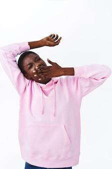 Retrato vertical de uma garota afro-americana elegante e preguiçosa com um capuz rosa, bocejo sonolento, tampa da boca aberta com o braço e alongamento, cochilou