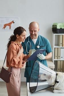 Retrato vertical de uma jovem conversando com o veterinário na clínica veterinária com um cachorro usando uma coleira protetora na mesa de exame