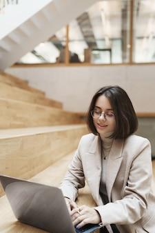 Retrato vertical de uma jovem mulher de cabelos curtos profissional e bem-sucedida numa jaqueta bege, digitando a mensagem para o cliente usando o laptop, trabalhando em um projeto remoto online, estudando ou trabalhando como freelancer.