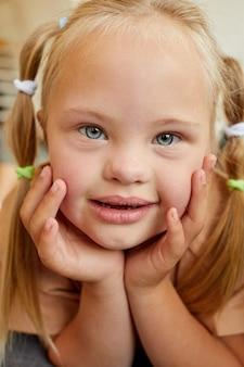 Retrato vertical de uma linda garota com síndrome de down sorrindo e enquanto estava deitada no sofá em casa