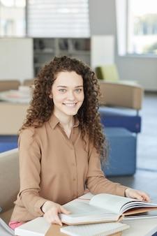 Retrato vertical de uma linda garota de cabelos cacheados sorrindo para a câmera enquanto estudava na biblioteca da faculdade