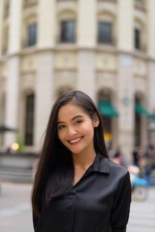 Retrato vertical de uma linda mulher de negócios asiática sorrindo ao ar livre na rua da cidade